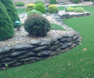 Artificial turf and dry stacked rock raised garden bed