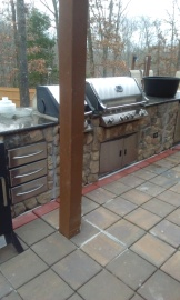 Custom outdoor kitchen with granite counters under an arbor