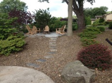 Gravel yard with native stone path leading to custom sitting are and firepit